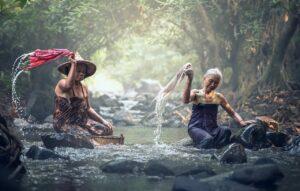 Frauen waschen am Fluss